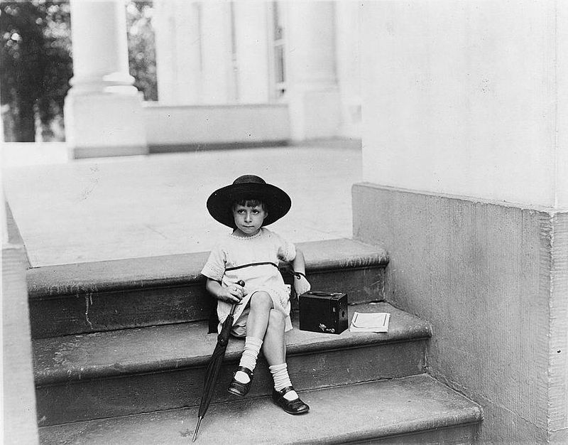 Young girl seated on the White House steps with a camera by her side June 1929