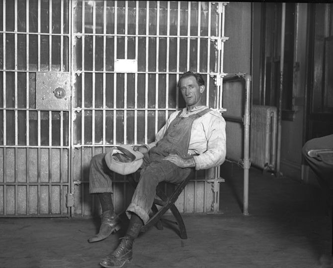 Clusc_8_1_00166426a_jCharles Wesley Way dressed in overalls, sitting in front of jail cell after his arrest for threatening to shoot oil workers in Los Angeles, Calif., 1925
