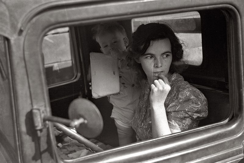 Farm wife and baby waiting in the car while her husband attends the auction. Oskaloosa, Kansas John Vachon 1938