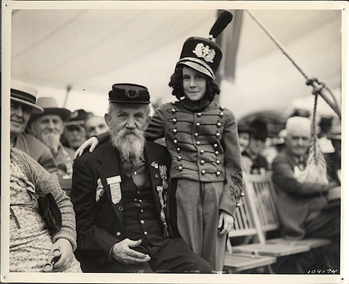 Annie Laurie, age nine, of Atlanta, GA, wears a cadet costume and stands in the embrace of William D. Welch (age 94) of Pittsburgh, PA