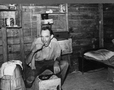 Migrant agricultural worker from Tennessee, formerly a railroad man, eating dinner in his shack, an old tool house. Homestead, Florida Marion Post Walcott 1939