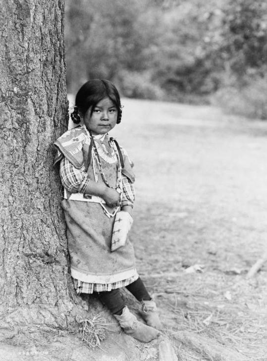 An Umatilla girl, full-length portrait, standing by tree, facing slightly right