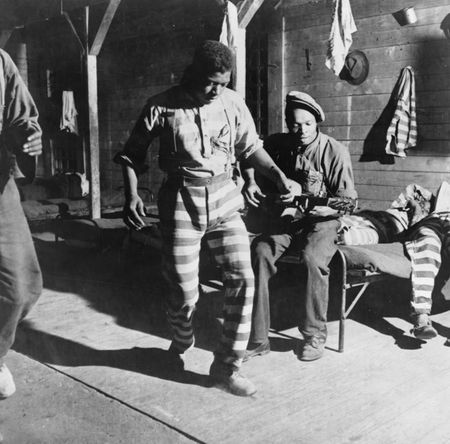 A prisoner dancing while another plays the guitar at a prison camp. Greene County, Georgia