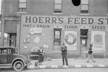 Waiting for a bus in front of feed store, Peoria, Illinois  Arthur Rothstein 1938