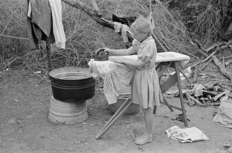 Child of white migrant worker ironing in camp near Harlingen, Texas r lee 1939
