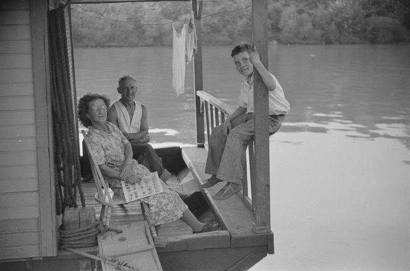Family on front porch of houseboat on river in Charleston, West Virginia