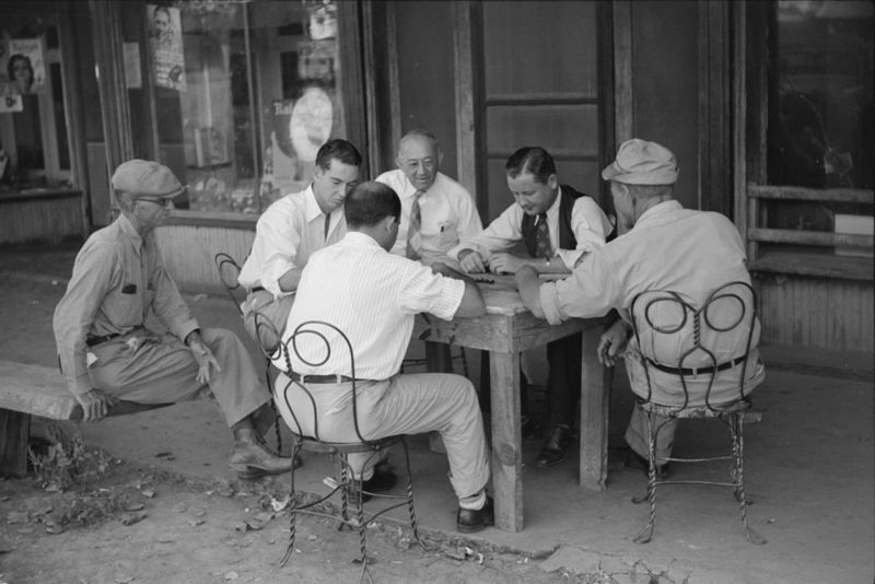 Playing dominoes or cards in front of drug store in center of town, in Mississippi Delta, Mississippi