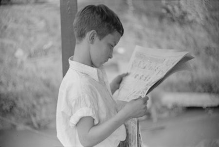 Son of man living on houseboat on river reading paper. Charleston, West Virginia