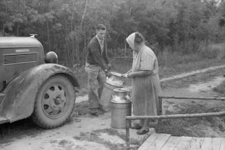 Truck driver picking up milk at Mrs. Howard's cut-over small farm. This is her main source of income. Aitkin County, Minnesota