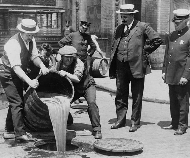 Agentes despejando bebidas alcoólicas no esgoto, E.U.A., anos 20